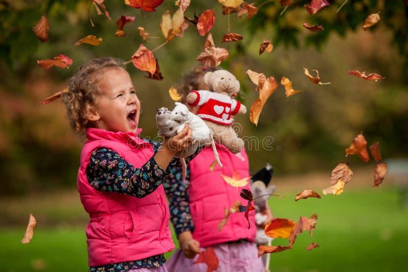 Eineiige Zwillinge, die Spaß mit Herbstlaub, blonde nette gelockte Mädchen, glückliche Familie, schöne Mädchen in den rosa Jacken stockfoto