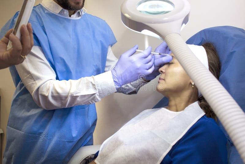In einem Ärztlichen Dienst unter dem Licht einer leistungsfähigen Lampe führt ein Doktor ein ästhetisches Verfahren mit einer Spr lizenzfreie stockbilder