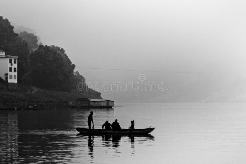 An einem bewölkten Tag schwimmt ein kleines Boot auf das Xin-` einen Fluss von China stockfotos