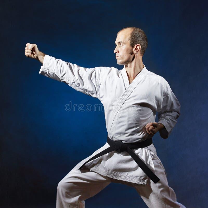 In einem Karategestell trainiert ein Mann eine formale Karateübung stockfotografie