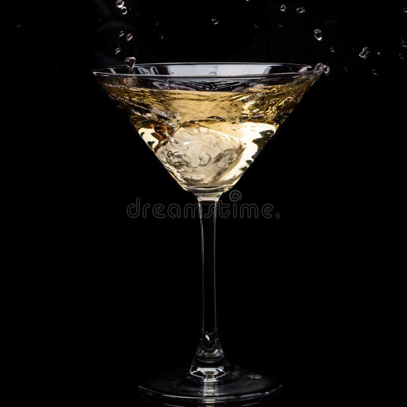 In einem Martini-Glas f?llt Wermuteis und spritzt mit R?ckg?ngen auf einem schwarzen Hintergrund lizenzfreie stockbilder