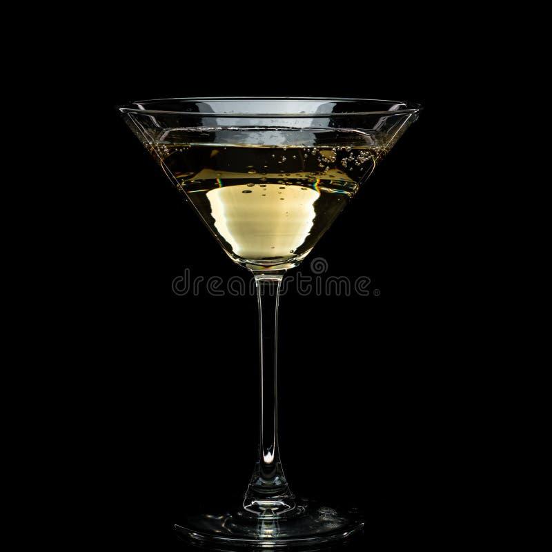 In einem Martini-Glas f?llt Wermuteis und spritzt mit R?ckg?ngen auf einem schwarzen Hintergrund stockfotografie