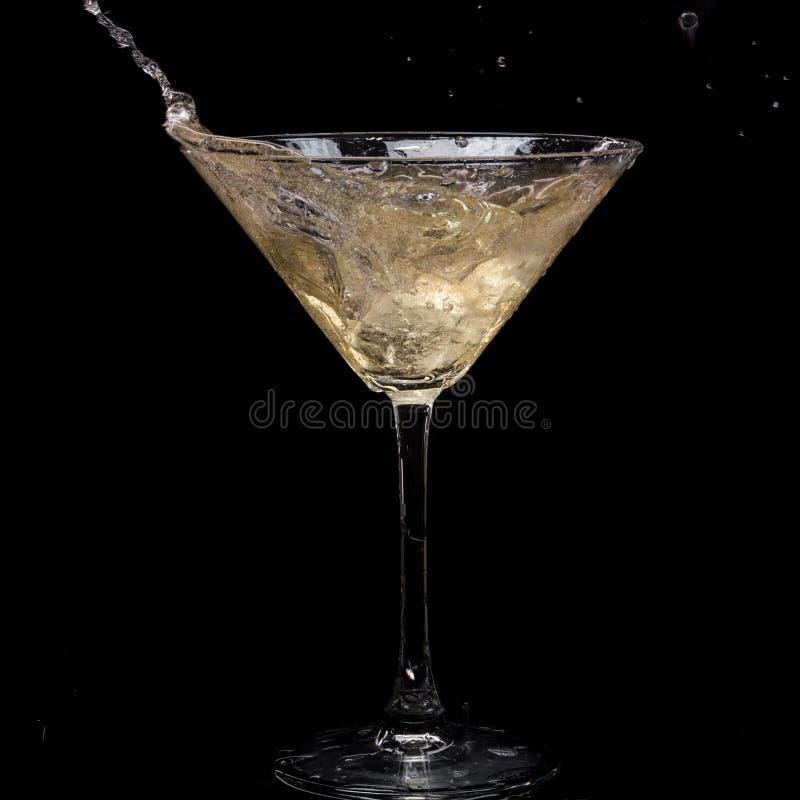 In einem Martini-Glas f?llt Wermuteis und spritzt mit R?ckg?ngen auf einem schwarzen Hintergrund lizenzfreies stockfoto