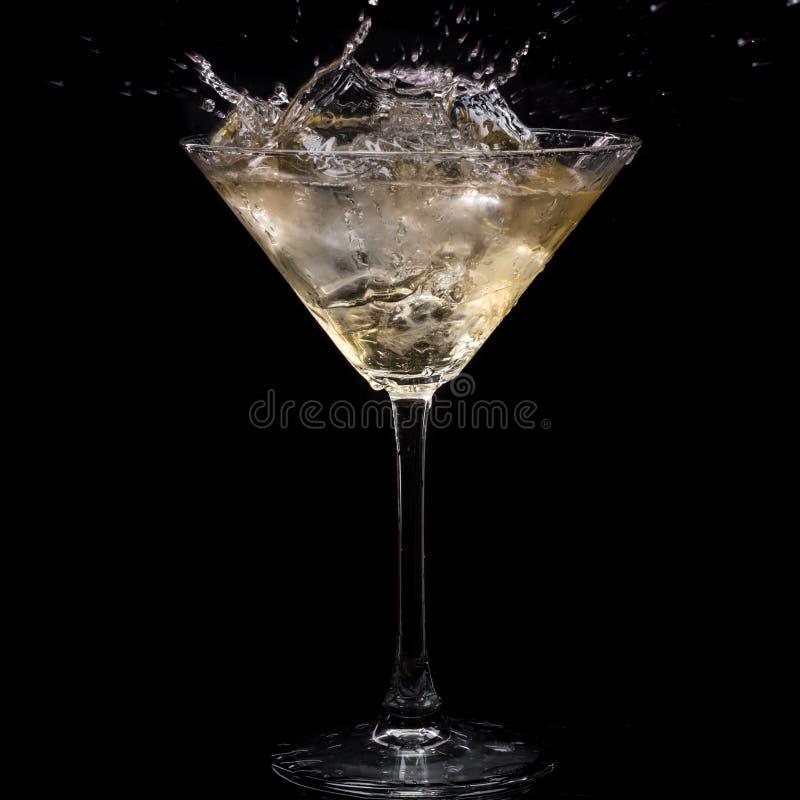 In einem Martini-Glas f?llt Wermuteis und spritzt mit R?ckg?ngen auf einem schwarzen Hintergrund lizenzfreies stockbild