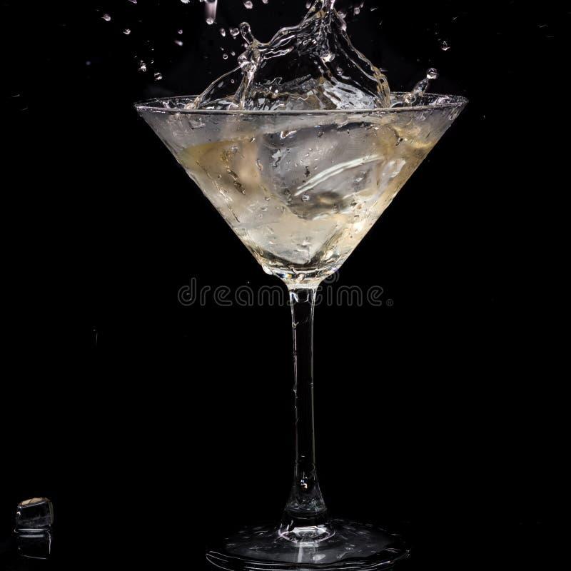 In einem Martini-Glas f?llt Wermuteis und spritzt mit R?ckg?ngen auf einem schwarzen Hintergrund stockfotos