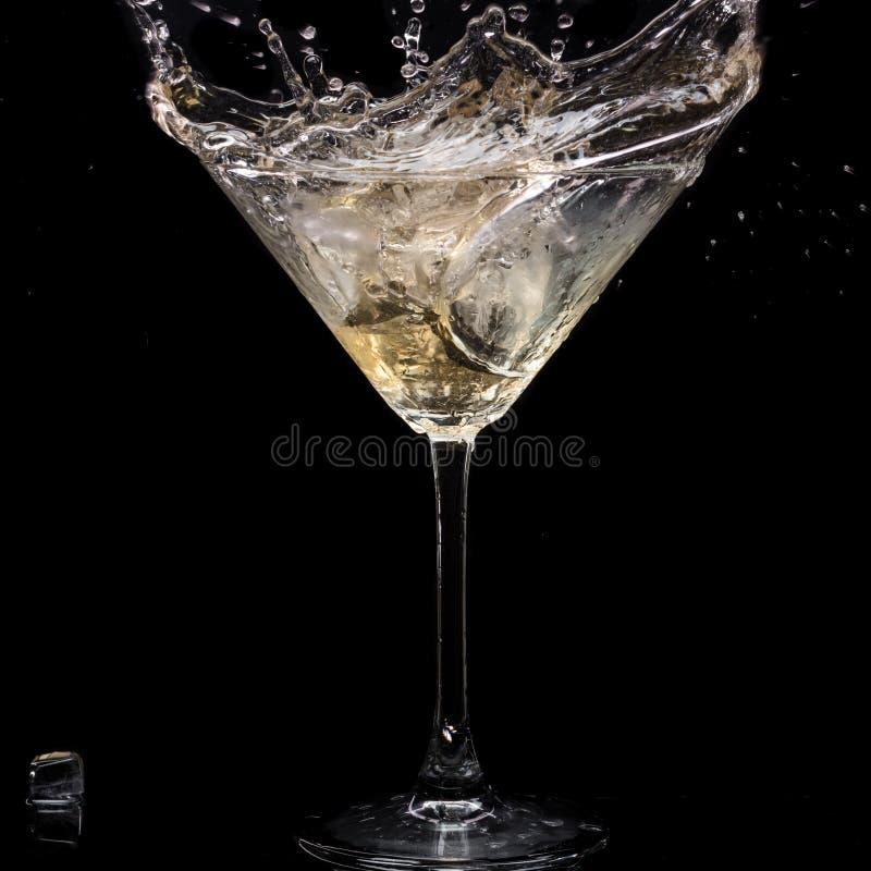 In einem Martini-Glas f?llt Wermuteis und spritzt mit R?ckg?ngen auf einem schwarzen Hintergrund lizenzfreie stockfotografie