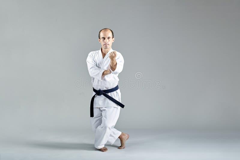 In einem niedrigen Karatestand tut ein Athlet formale Karateübungen stockfotos