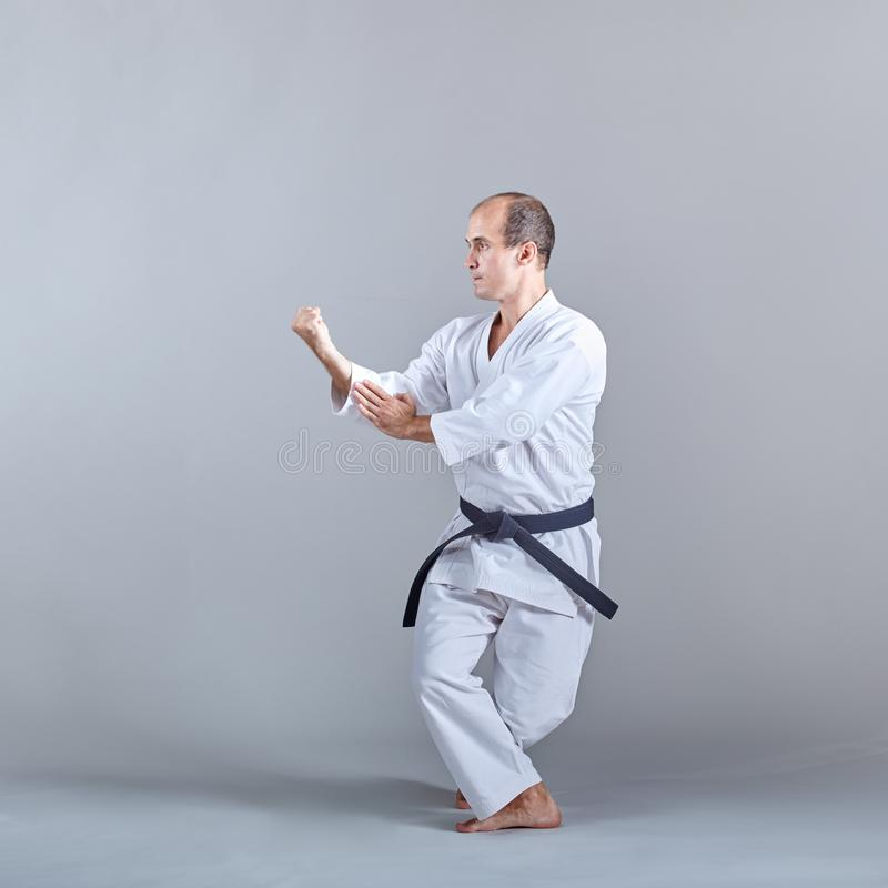 In einem niedrigen Stand bildet ein Athlet eine formale Karateübung aus stockbild