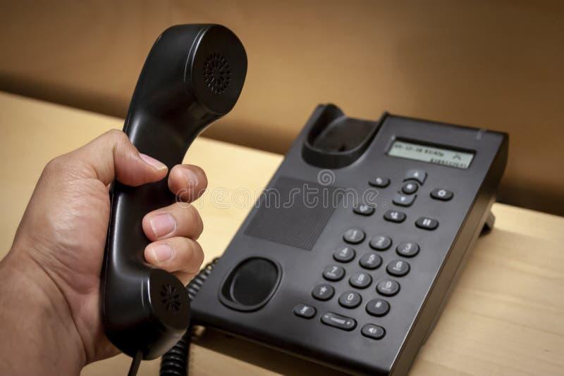 Einen Anruf in einem schwarzen Telefon aufheben stockfotografie