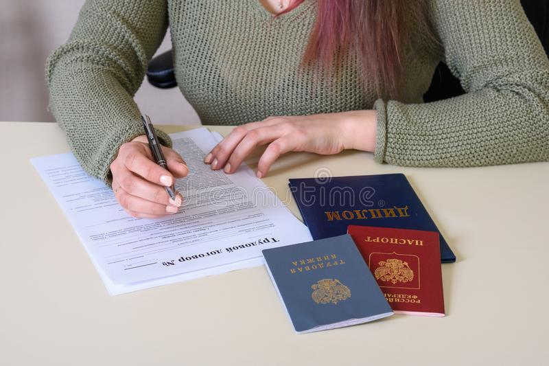 Einen Anstellungsvertrag auf dem Tisch ergänzen und eine Beschäftigungszahl, Pass und Diplom stockfoto