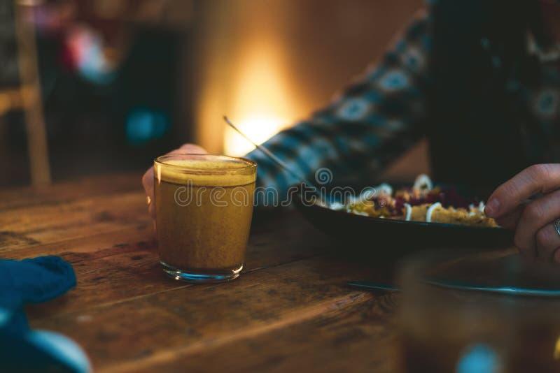 Einen Kaffee und das Essen der Nahrung des strengen Vegetariers trinken stockfotos