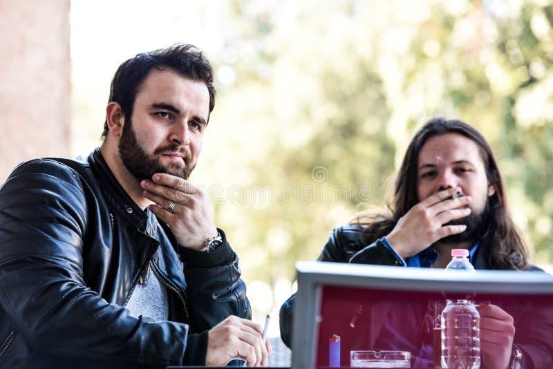 Einen Rauch mit einem Bier haben Beleuchten einer Zigarette lizenzfreie stockfotografie