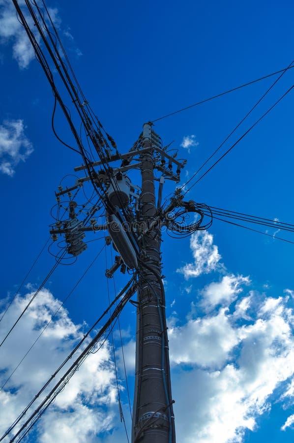 Einen Strommast mit blauem Himmel im Hintergrund oben schauen stockfotos