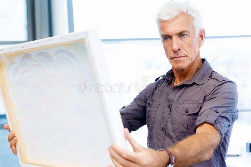In einer Galerie stehender und erwägender Mann stockbild