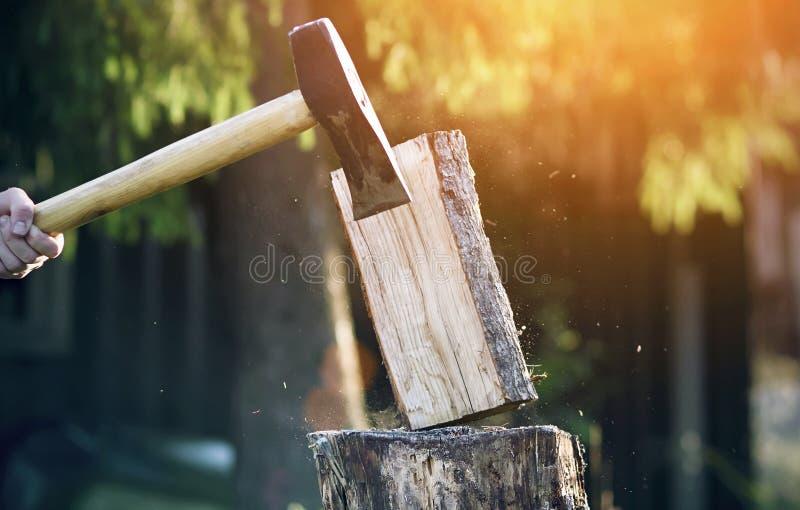 In einer Sägemühle mitten in dem Wald schneidet der Holzfäller Klotz mit einer scharfen langen Axt stockfotos