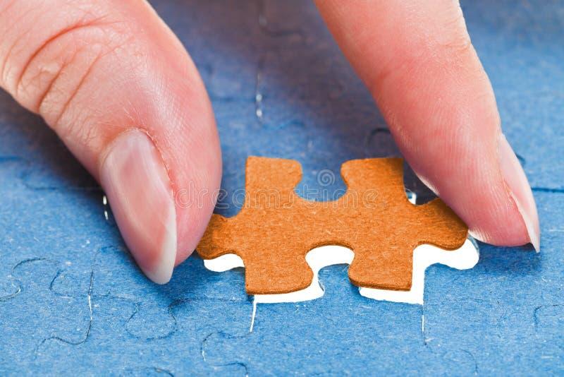 Einfügung des letzten orange Stückes des Puzzlespiels lizenzfreie stockfotos