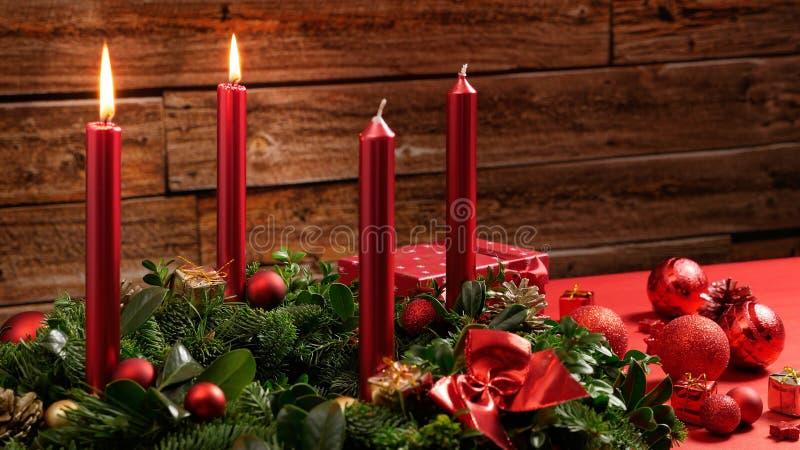 Einführungskranz mit zwei brennenden Kerzen und festliche Dekoration vor einer hölzernen Wand der Weinlese lizenzfreies stockfoto