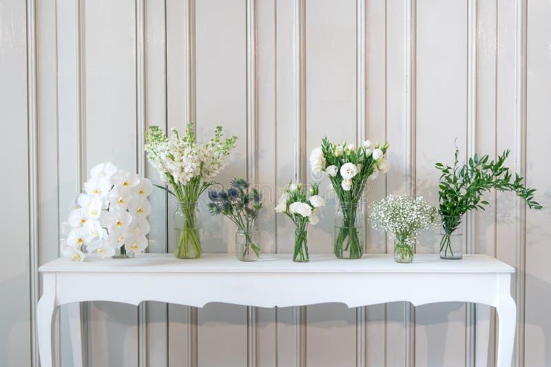 Einfach Zusammensetzung der unterschiedlichen weißen Blume im Vase auf weißer Weinlesetabelle lizenzfreie stockfotos