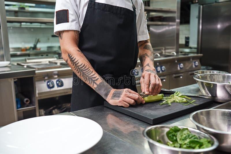 Einfache Aufgabe Schließen Sie oben von den männlichen Händen mit den schönen Tätowierungen, die Gurke für Salat bei der Stellung lizenzfreie stockfotografie