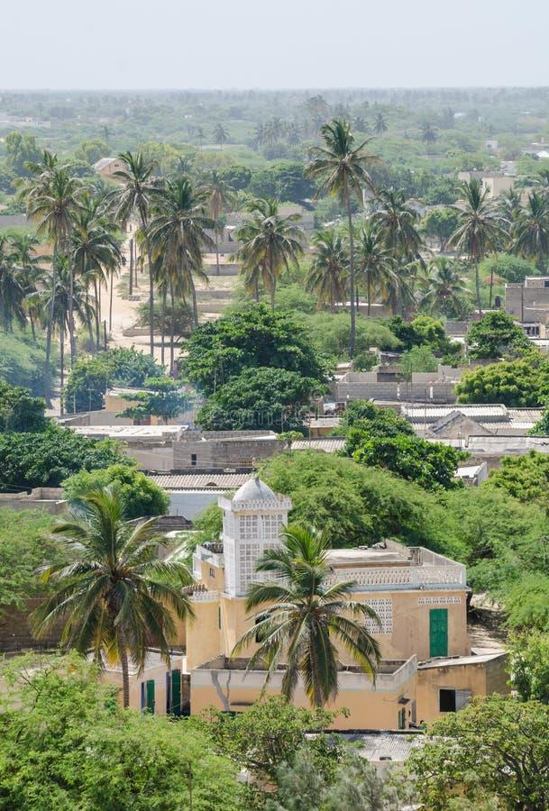 Einfache gelbe Moschee umgeben durch grüne Vegetations- und Palmen an der Küstenstadt Ndiebene, Senegal lizenzfreie stockfotos