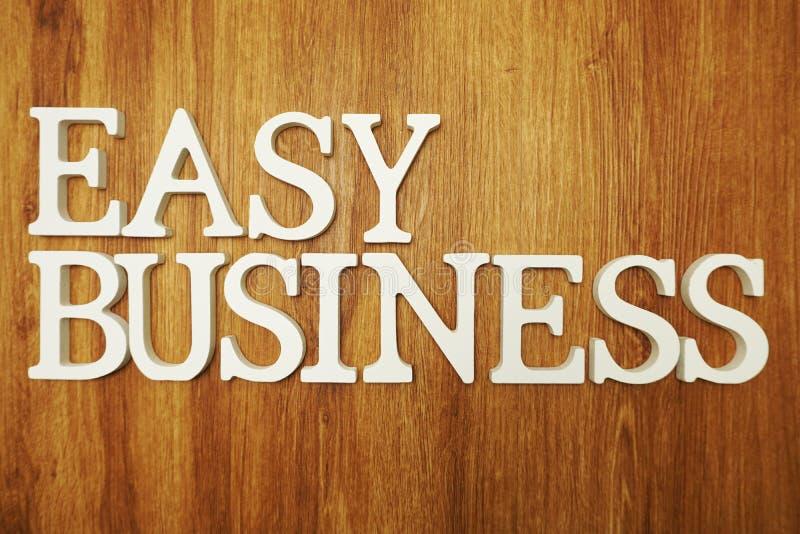 Einfache Geschäftswort-Alphabetbuchstaben auf hölzernem Hintergrund stockfotografie