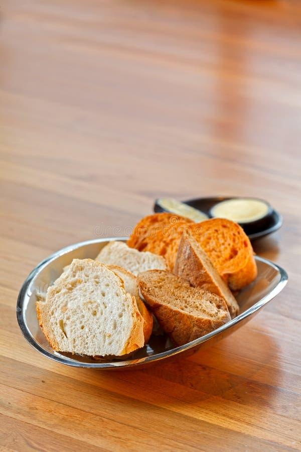 Einfache neue Stangenbrotbrotscheiben in der Platte auf Holztisch mit Butter hinten stockbilder
