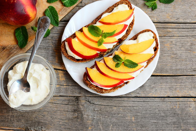 Einfache Roggensandwiche mit Weichkäse und neuen Nektarinenscheiben Helle Sommersandwiche auf einer Platte Hölzerner Hintergrund  lizenzfreies stockbild