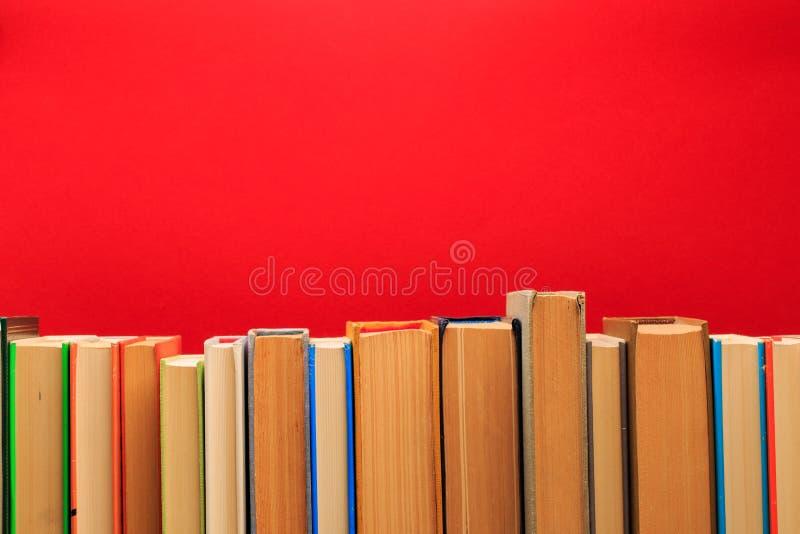 Einfache Zusammensetzung von Büchern des gebundenen Buches, roh von den Büchern auf hölzerner Plattformtabelle und rotem Hintergr stockfoto
