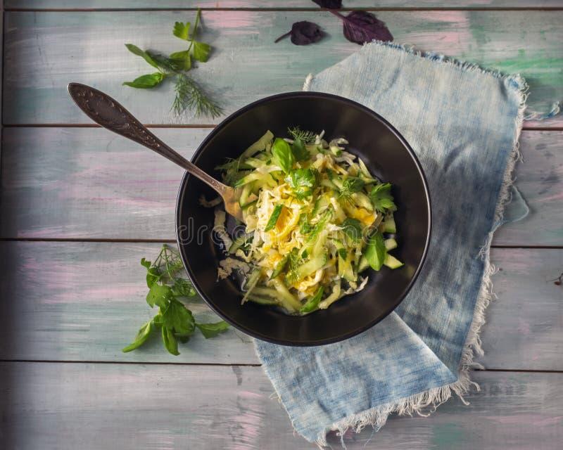Einfacher Gemüsesalat, der Kohl, Gurke und nach grünem Pfeffer in einem runden tiefen schwarzen Teller sucht, der auf einer Denim stockbild