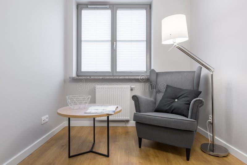 Einfacher Raum mit grauem Lehnsessel stockfoto