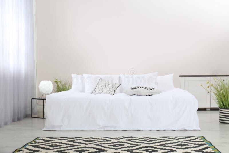 Einfacher Rauminnenraum mit großem bequemem Bett stockbild