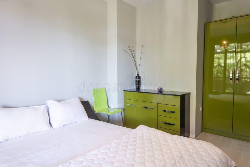 Einfacher Schlafzimmerinnenraum mit großem bequemem Bett und grünen Möbeln Innenphotographie stockfoto