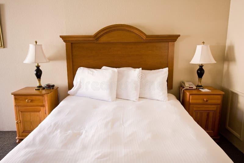 Einfaches Bett, Headboard, nightstands, Lampen lizenzfreie stockfotografie