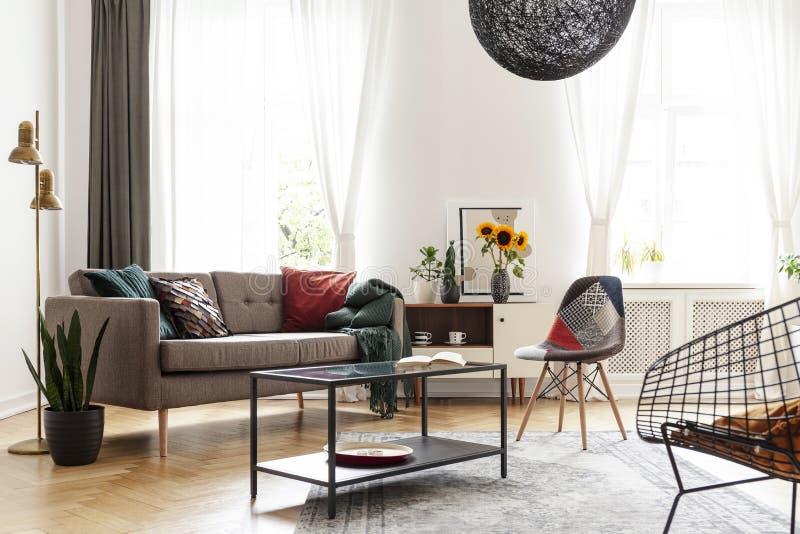 Einfaches braunes Sofa mit Kissen in einem eklektischen, weißen Wohnzimmerinnenraum mit dem natürlichen Licht, das durch große Fe stockfotos