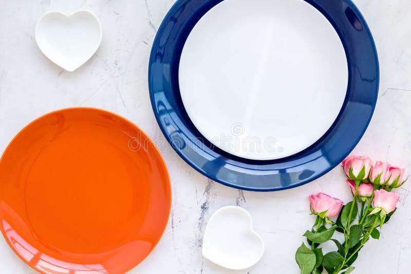 Einfaches Farbgedeck für Feier mit Rosen, orange und blaue Platten und Herz-förmige Untertassen auf Steintabelle stockbilder