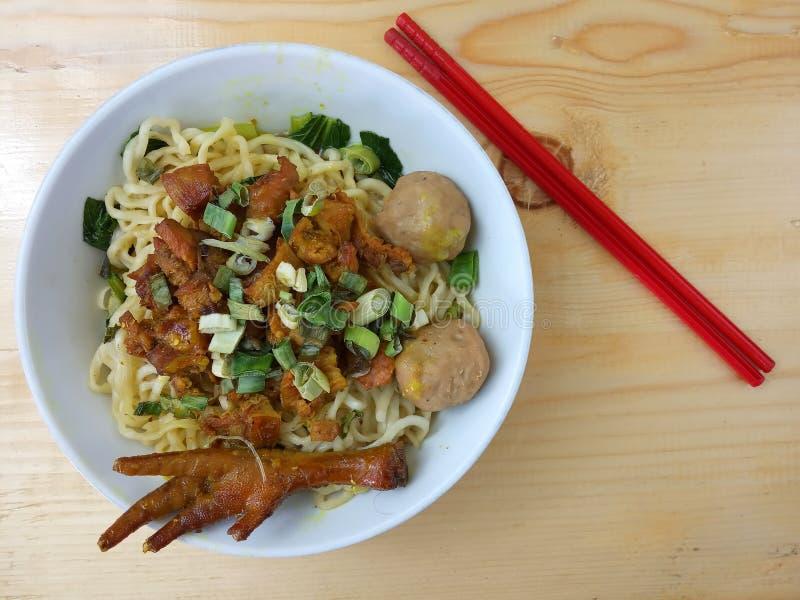 Einfaches Foto, flache Lage, köstliche Mie Ayam, Hühnernudel an der weißen Schüssel und am roten Plastikessstäbchen am Holztisch  stockbild