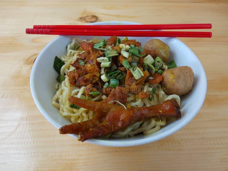 Einfaches Foto, flacher Lay, köstliche Mie Ayam, Chicken Noodle in weißer Schüssel und roter Plastikschlauch am Holztisch aus Ind stockfotos