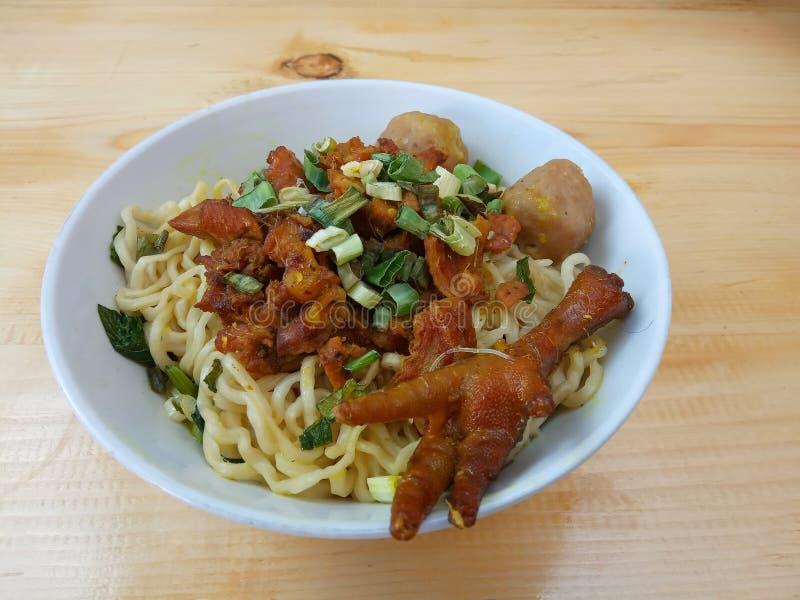 Einfaches Foto, flacher Lay, köstliche Mie Ayam, Chicken Noodle in weißer Schüssel und roter Plastikschlauch am Holztisch aus Ind lizenzfreies stockbild