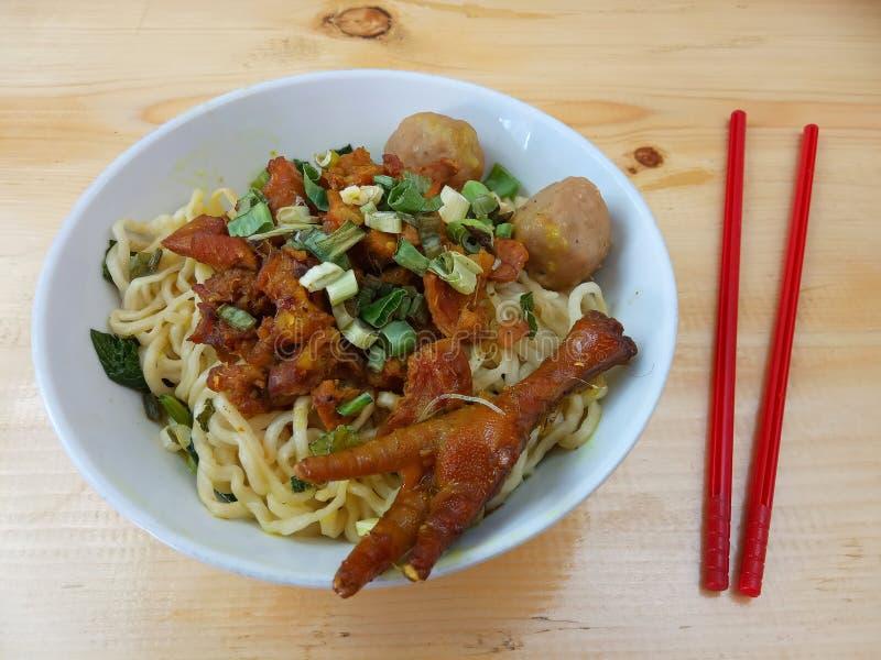 Einfaches Foto, flacher Lay, köstliche Mie Ayam, Chicken Noodle in weißer Schüssel und roter Plastikschlauch am Holztisch aus Ind stockfotografie