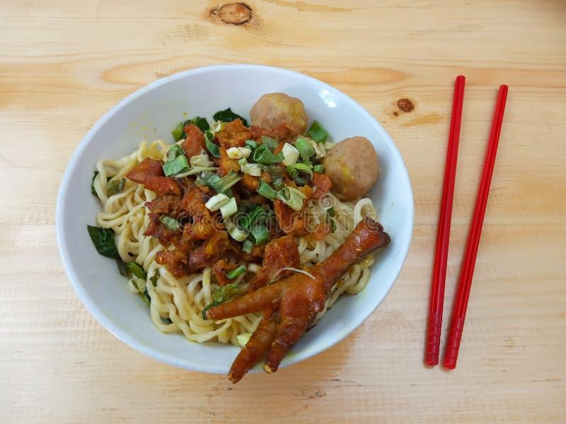 Einfaches Foto, flacher Lay, köstliche Mie Ayam, Chicken Noodle in weißer Schüssel und roter Plastikschlauch am Holztisch aus Ind lizenzfreie stockfotos