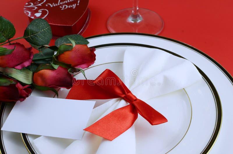 Einfaches Gedeck für Valentinstag mit Schwarzweiss-Porzellan, rote Rosen der Seide, ein Bogen auf einem roten Hintergrund Glänzen lizenzfreie stockbilder