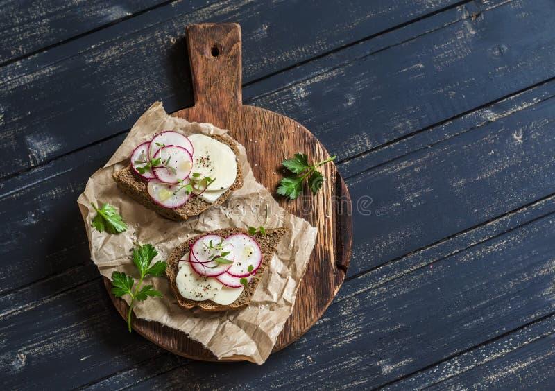 Einfaches gesundes Frühstück - Käserettich und Roggenbrotsandwich auf einem rustikalen hölzernen Schneidebrett stockbilder