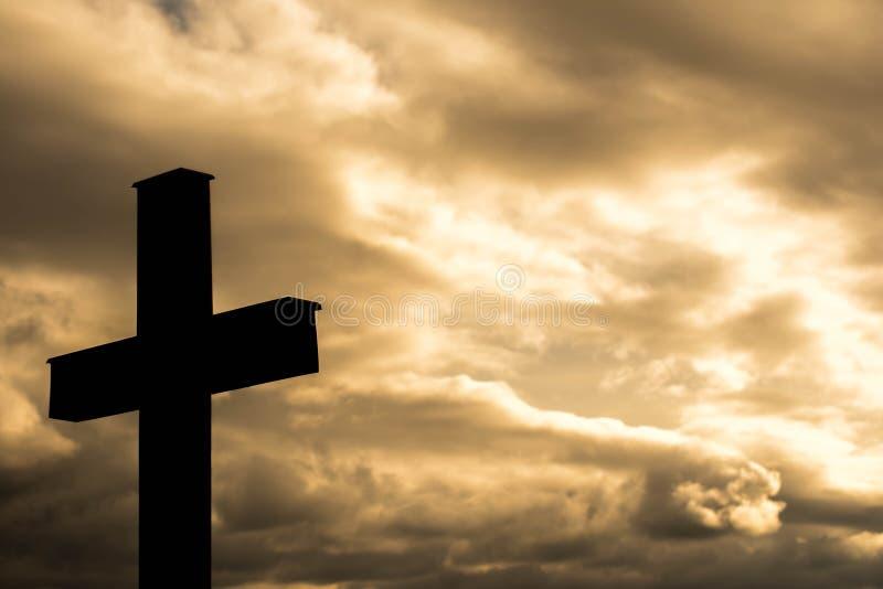 Einfaches hölzernes katholisches Querschattenbild, drastische orange Sturmwolken im Hintergrund, stockbilder