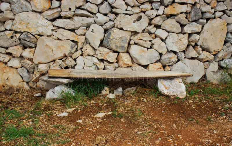 Einfaches hölzernes Seat mit Steinwand lizenzfreie stockfotos