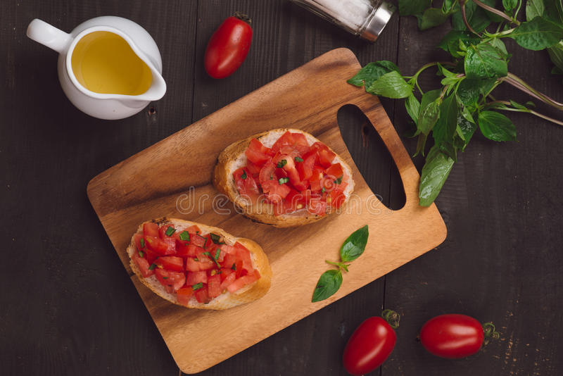Einfaches italienisches appetitanregendes bruschetta mit Tomate, auf hölzernem tabl lizenzfreie stockbilder