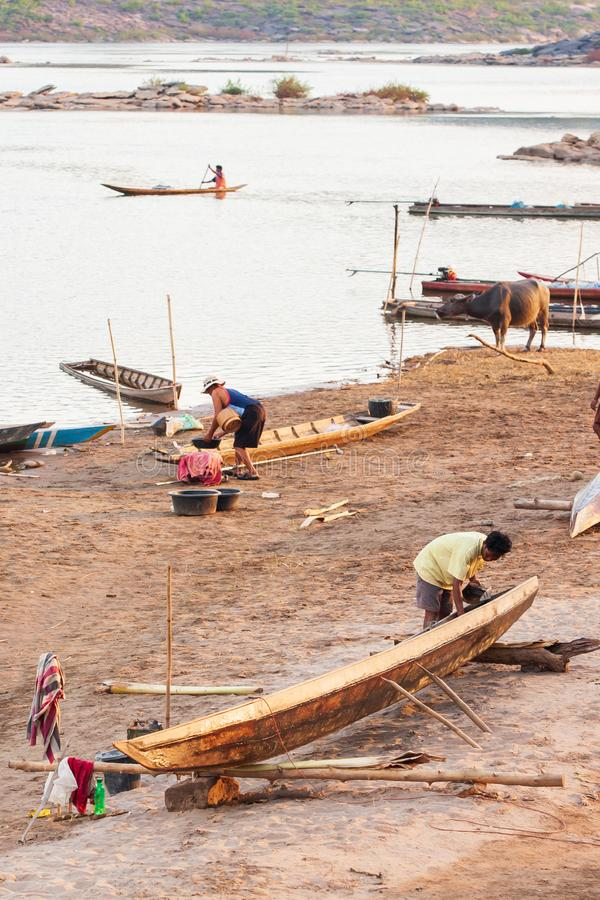 Einfaches Leben, Stamm Bru-Dorf auf Flussufer, Schiffsreparaturteam, das hölzernes Boot in der lokalen Werft, Büffel fischend rep lizenzfreie stockbilder