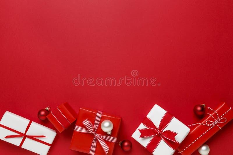 Einfaches, modernes Rot u. Geschenke der weißen Weihnacht stellt sich auf rotem Hintergrund dar Festliche Feiertagsgrenze lizenzfreies stockfoto