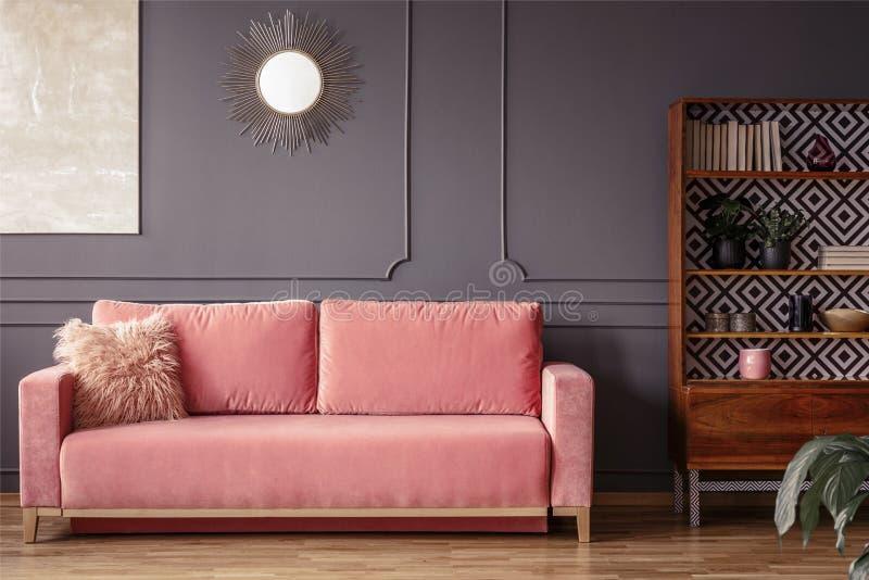 Einfaches, rosa Sofa mit einem Pelzkissen nahe bei einem hölzernen Schrank herein lizenzfreies stockbild