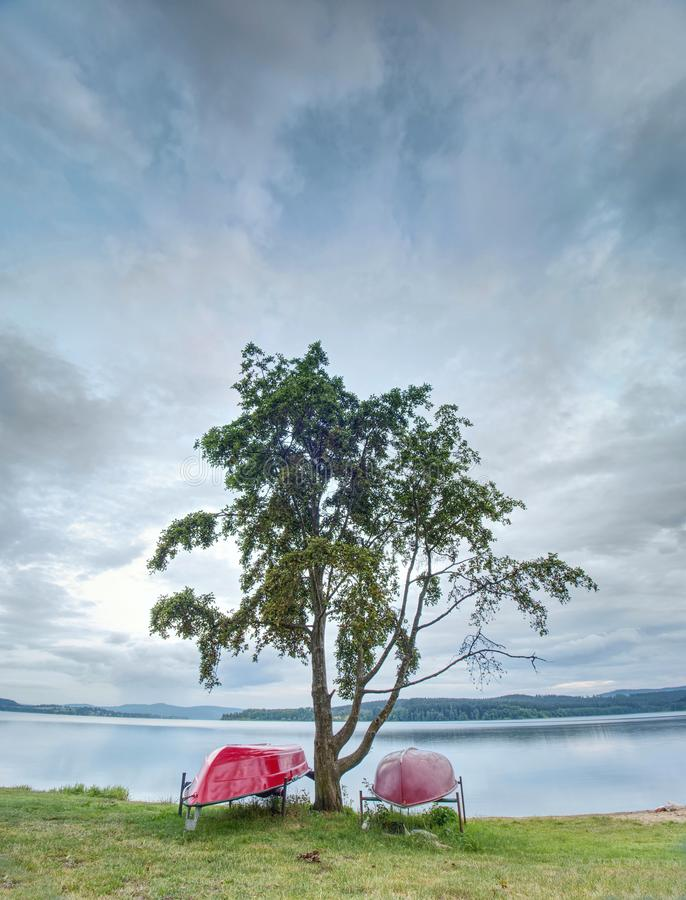 Einfaches Ruderboot gestapelt am See umgedreht Leerer Strand stockbilder