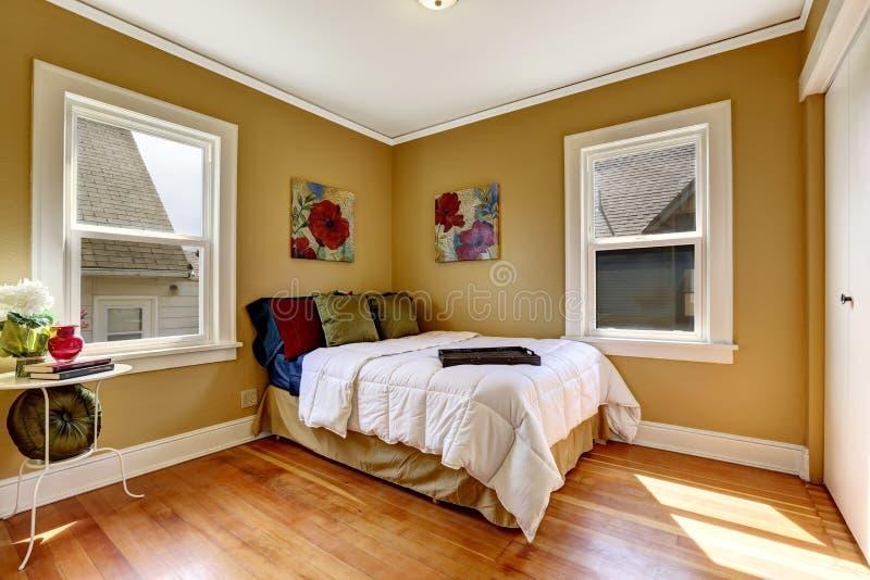 Einfaches Schlafzimmer mit Einzelbett in der bunten Bettwäsche stockbilder